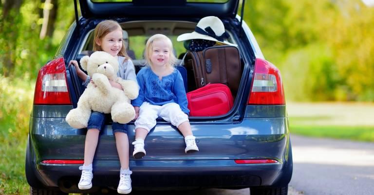 Kinderen achterin de auto op vakantie