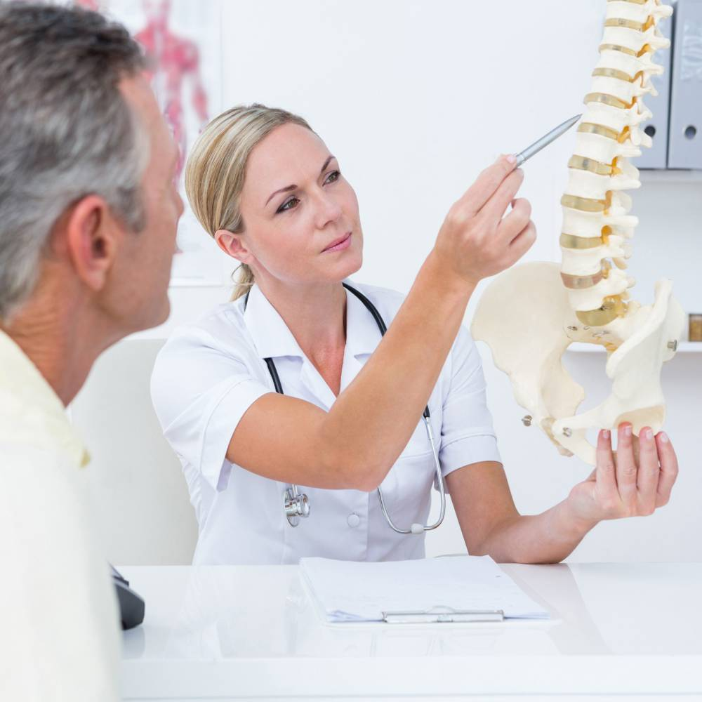 Dokter wijst naar ruggenwervel